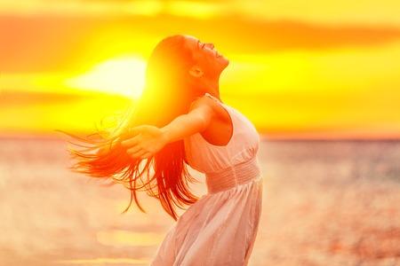 Mulher feliz que sente livre com os braços abertos na luz do sol no por do sol da praia. Liberdade e despreocupada garota gozando a vida. Mulher bonita no vestido branco para o sucesso, a saúde, a esperança e o conceito de fé.