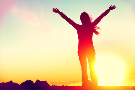 Happy celebrating winning success woman at sunset or sunrise standing elated with arms raised up above her head in celebration of having reached mountain top summit goal during hiking travel trek. Stock Photo - 65499163