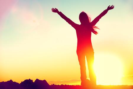 Heureux de célébrer la réussite de la femme au coucher du soleil ou au lever du soleil debout exalté avec les bras levés au-dessus de sa tête en l'honneur d'avoir atteint le sommet du sommet de la montagne au cours de randonnée randonnée.