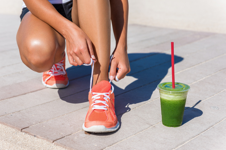Running woman athlete runner getting ready for beach morning run by tying shoe laces of running shoes with green vegetable smoothie breakfast. Closeup on feet. Fitness and healthy lifestyle concept. Stock Photo