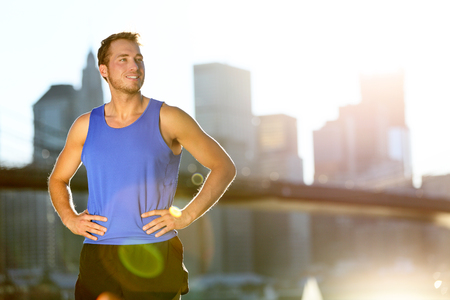 outdoor outside: Sport athlete man running looking away at New York City - Brooklyn Bridge and Manhattan skyline copy space. Active healthy lifestyle fit fitness runner outside training fitness workout outdoor in NYC. Stock Photo