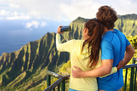 destination scenic: Couple on travel destination vacation relaxing together. Happy young adults tourists taking pictures with smartphone of amazing scenic view of na pali coast at Kalalau lookout on Kauai, Hawaii, USA. Stock Photo