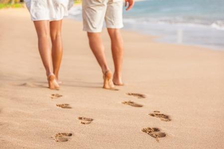 Plażowa para relaksuje przy zmierzchu chodzić bosym. Skoncentruj się na śladach w złotym piasku. Zbliżenie nóg. Romantyczne wakacje na plaży. Młodzi ludzie z tyłu odchodzą w kierunku szczęścia.