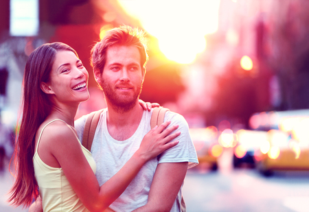 asian lifestyle: Happy Asian woman, Caucasian man multiethnic couple relaxing in sunset laughing smiling on urban city street in New York city, USA. Young people in love living a modern lifestyle.
