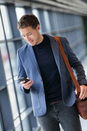 스마트 폰에 남자 - 공항에서 젊은 비즈니스 남자 문자 메시지. 스마트 폰 응용 프로그램 사무실 건물 또는 공항 내 행복 미소를 사용하여 캐주얼 도시