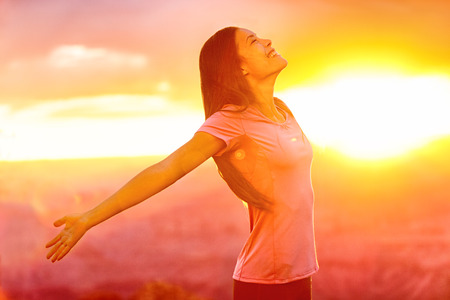 spirituality: Happy people - carefree woman enjoying free nature at sunset. Freedom, serenity, wellness and spirituality concept - Asian girl with open arms in ecstatic enjoyment praising life to the sky. Stock Photo