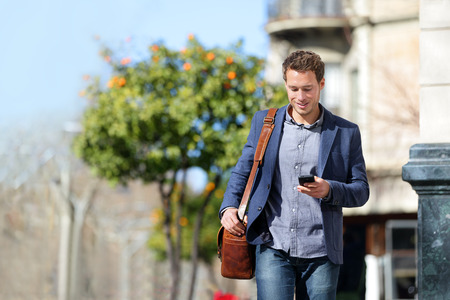 young businessman: Young urban businessman professional on smartphone walking in street using mobile phone app texting sms message on smartphone wearing smart casual jacket. City lifestyle commute person walking. Stock Photo