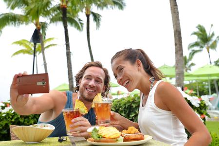 Glückliche junge zwischen verschiedenen Rassen Paare, die auf Sommerferien Essengehen lokale Speisen Mahlzeit im Freien Restaurant mit Terrasse genießen einen selfie Bild mit Handy für Urlaubserinnerungen nehmen.