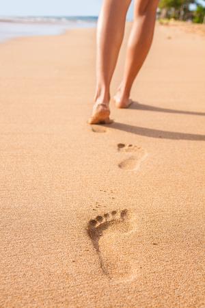 砂浜の足跡女性足が裸足で歩きます。砂の足跡を残す金色の砂のビーチの上を歩く女の子を旅行します。女性の足や日没時足のクローズ アップの詳細。 写真素材 - 65499474