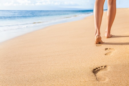 Beach travel - woman relaxing walking on sand beach leaving footprints in the sand. Closeup detail of female feet and legs on golden sand on Kaanapali beach, Maui, Hawaii, USA. Stock Photo