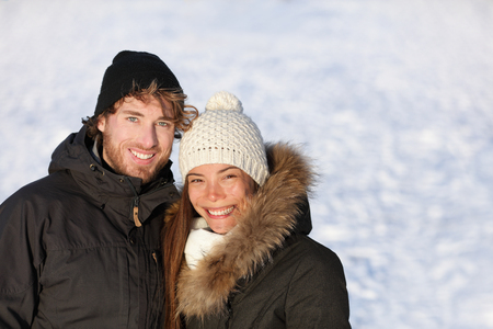 outerwear: Happy winter interracial couple outdoors portrait. Cute young adults smiling in warm outerwear knit hat and down coats outside. Asian chinese woman, Caucasian man. White snow ice background texture.
