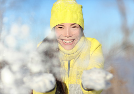 white playful: Winter fun girl playful throwing snow at camera portrait. Asian woman face closeup with yellow beanie knit hat and white gloves playing with snowflakes. Happy snowball snow fight wintertime concept.