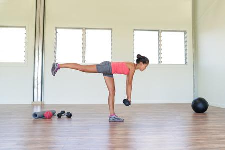 haciendo ejercicio: entrenamiento de la fuerza de la mujer en el gimnasio de la corva ejercicio y músculos de la espalda con una sola pierna exercicses muerto rumano con pesas pesas. Asiático, solo en el interior de la muchacha en la sala de fitness.