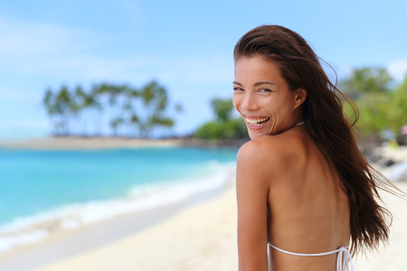 brown skin: Cute happy Asian chinese woman laughing with perfect smile on paradise vacation tropical beach travel destination. Beautiful multiracial brunette girl in bikini sunbathing on ocean background. Stock Photo