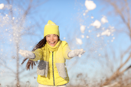 outerwear: Winter fun girl playful throwing snow at camera outside. Happy Asian woman with arms up in the air playful on a sunny day in wintertime wearing warm hat, scarf and gloves yellow outerwear.