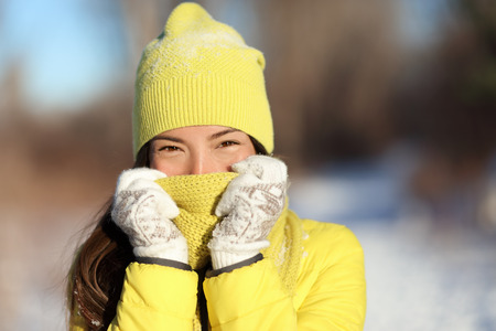 cold season: Winter freezing woman covering face from cold. Skincare concept. Cute Asian girl happy holding scarf with gloves over nose and mouth to protect from the frost. Warm outerwear for wintertime season. Stock Photo