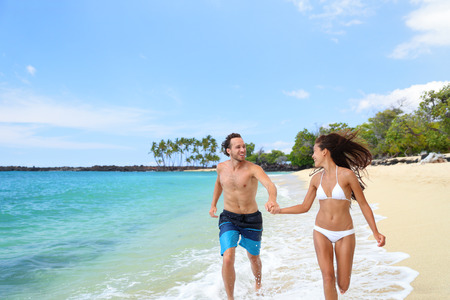 young happy couple: Happy couple laughing together holding hands running having fun splashing water in the ocean waves. Young beautiful fit slim body people enjoying their happy lifestyle in paradise destination beach.