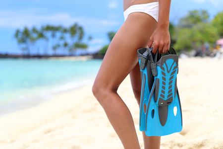 snorkelling: Closeup of sexy legs of bikini woman with snorkeling equipment standing looking at ocean. Girl holding blue flippers ready for snorkel. Scuba diving beach vacation concept. Stock Photo