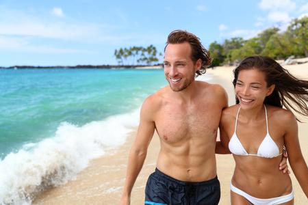 Schöne sexy Bräune Menschen. Glückliche junge zwischen verschiedenen Rassen Paare mit schlanken und gesunden Körper auf tropisches Paradies Strand während der Sommerferien erholsamen Urlaub zu Fuß. Reisen Entspannung Sonne Hautpflege-Konzept.