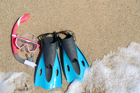objects equipment: Beach vacation activity: snorkel equipment for women. Scuba diving and snorkelling. Blue Flippers, pink mask, snorkel on sandy texture background. Objects lying on sand.
