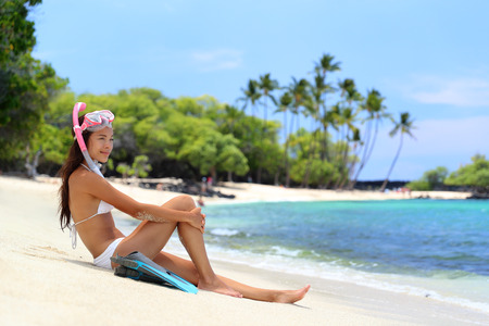 sun tanning: Beach vacation snorkel girl snorkeling with mask and fins. Bikini woman relaxing on summer holidays sitting after snorkelling with snorkel tuba and flippers sun tanning.