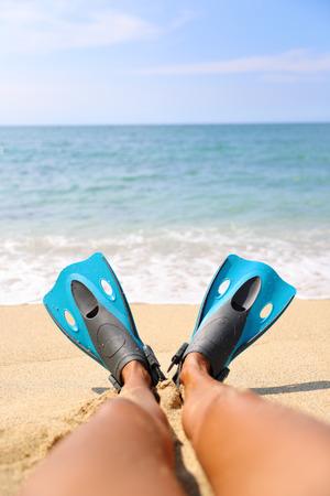 fun activity: Foot selfie: snorkeler relaxing on beach overlooking the ocean with legs showing blue flippers snorkel equipment lying on sand. Tropical getaway vacation. Watersport fun activity: snorkeling.
