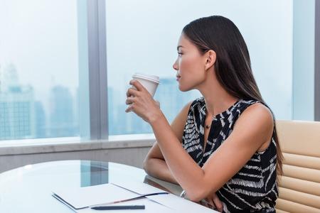 事務所女の窓から街の景色を見てリラックスした幸せのコーヒーを飲みます。キャリア目標を考えて仕事やビジネス デスクで仕事の物思いにふける