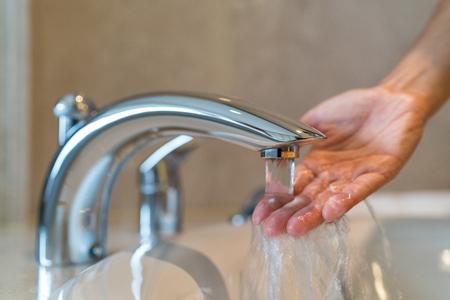 Frau, die ein Bad zu Hause Kontrolle Temperatur berühren, die Wasser mit der Hand ausgeführt wird. Nahaufnahme auf die Finger unter heißem Wasser aus einem Wasserhahn eines Waschbeckens oder einer Badewanne im Haus Badezimmer