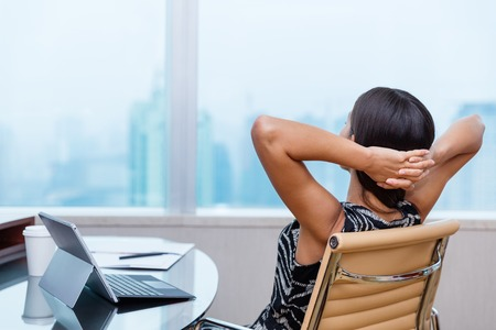 Business woman relaxing working at office desk laid back resting on chair with hands behind head. Work satisfaction businesswoman taking break after goal success or enjoying her job achievement. Stock Photo