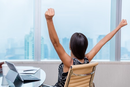 happy work: Winning office worker working woman with arms raised up outstretched in success of career goal achievement. Happy successful businesswoman looking at city view in work window.