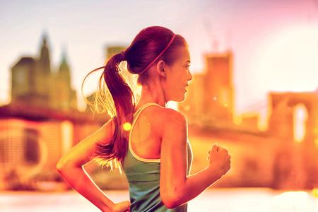 Lopende vrouw Aziatische runner in de stad New York zonsondergang. Runner joggen in het zonnige helder licht. Vrouwelijke fitness model opleiding buiten in New York City met skyline en Brooklyn Bridge op de achtergrond.