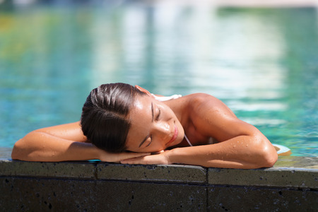 mimos: Woman relaxing sunbathing in infinity swimming pool at health spa retreat. Luxurious body care pampering Serene Asian young lady enjoying sun time at resort hotel facilities. Tranquility and comfort.