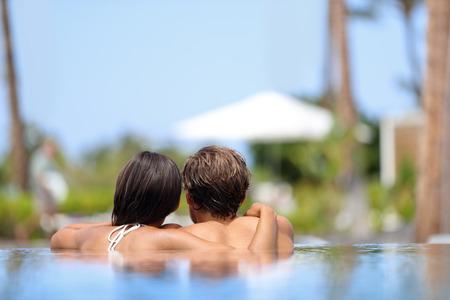 Flitterwochen-Paar in einem Infinity-Pool in Luxus-Resort Spa Retreat Strand Ziel entspannt zusammen. Luxushotel Reise Urlaub. Unkenntlich Menschen entspannt die Sommerferien genießen. Standard-Bild