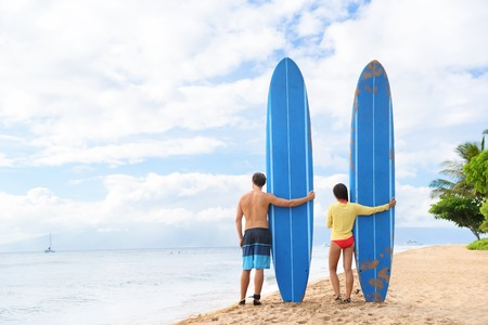 Deux personnes jeune couple debout surfeurs avec de longues planches de surf bleu sur hawaii plage Kaanapali après la classe de surf. activité surf sport Fun sur la plage de Maui touristique pour les vacances d'été.