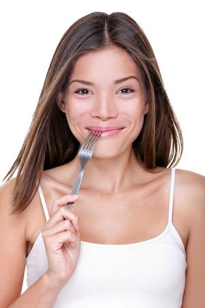 comida rica: La mujer asiática hermosa de la mujer mordiendo tenedor en el hambre con ganas de comer buena comida. concepto del foodie. Niña china feliz de dieta de pérdida de peso saludable o alimento delicioso sabroso.