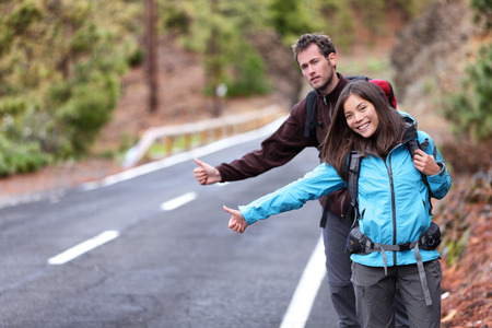 hitch hiker: Travel hikers couple showing thumbs up on street for hitchhiking during road trip. Happy young interracial backpackers hitchhikers waiting for a rideshare, sharing a ride on vacation holidays.