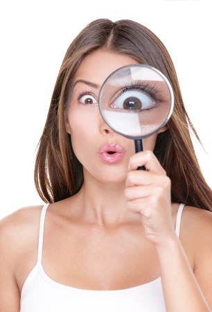 clues: Shocked woman looking through a magnifying glass. Funny surprised Asian girl astonished discovering clues through a magnifying glass, isolated on white background. Big eye closeup.