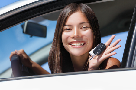 Happy Asian girl teen driver showing new car keys. Young woman smiling driving new car holding key. Interracial ethnic woman driver holding car keys driving rental car. Standard-Bild