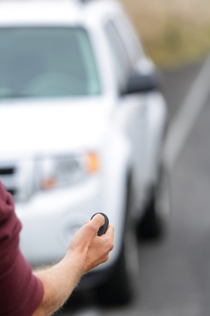 unlocking: Person opening door starting car with remote key ignition starter. Car remote control key fob. Man driver unlocking car door with unlock keyless system. Car vacation rental or driver owning new car. Stock Photo