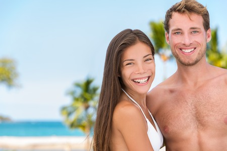 suncare: Sexy bikini sun tan couple on beach vacation. Good looking interracial models tanning on tropical holiday background. Asian woman, handsome man relaxing. Skincare solar protection beauty concept.