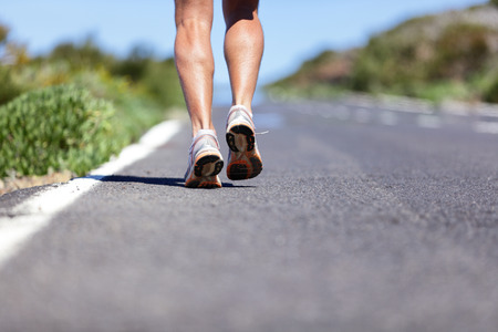Road to success. Runner with determination running long distance endurance run on marathon race road. Closeup of legs and running shoes with copy space on path background. Man running shoes. Imagens