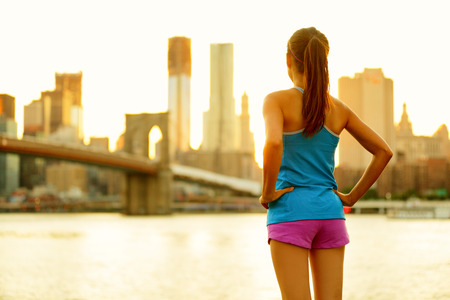 activewear: New York city lifestyle active people living an urban active life. Fitness healthy woman runner relaxing after running outdoors enjoying view of Brooklyn Bridge.