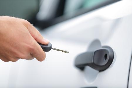 unlocking: Man opening unlocking door with car key. Car keys closeup of hand holding key to lock or unlock doors of white car travel vacation rental or driver owning new car. Stock Photo