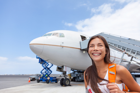 Woman tourist getting out of airplane at airport. Asian girl passenger walking out of stairs after plane landing arrival at airport at summer destination travel. Tourism concept.