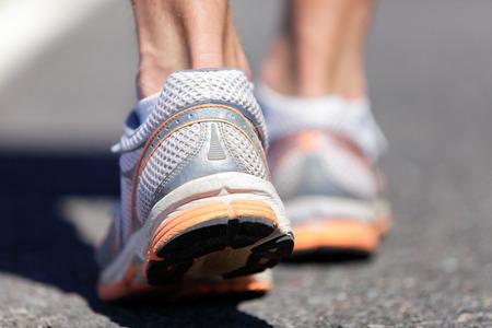 Loopschoen close-up van de mens die op weg met sportschoenen. Weg naar succes. Runner training cardio te oefenen, wandelen of start van de run op de marathon ras. Voeten gezondheid, hiel zorg.