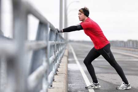 Man runner stretching legs before exercise run outdoors in city urban street during winter. Athlete wearing smartwatch, phone armband for music app and warm gloves, headband, long tights underwear.