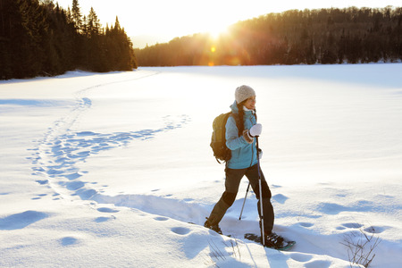 la actividad de deportes de invierno. Caminante de la mujer que va de excursión con el morral y snowwhoes raquetas de nieve en rastro del bosque de nieve en Quebec, Canadá al atardecer. Hermoso paisaje con árboles de coníferas y la nieve blanca. Foto de archivo