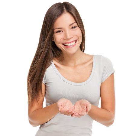 Dlaní baňkování koncept. S úsměvem asijský žena studio portrét na bílém pozadí ukazuje něco na dlaně otevřených oběma rukama drží za objekt kopie vesmíru. Reklamní fotografie