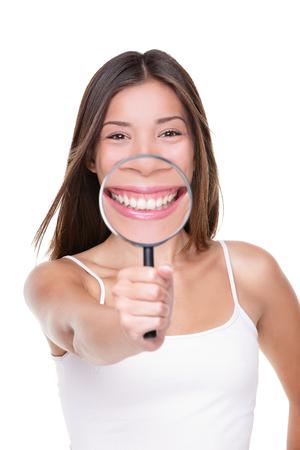 Mulher engraçada que mostra o sorriso perfeito e os dentes brancos com a lupa para o conceito dental do close up. A menina asiática que inspeciona detalhes de boca que mostram o dente saudável importa-se para o dentista.