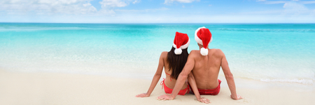 Christmas beach vacation holidays santa hat couple relaxing from behind sitting on white sand panorama banner background with ocean copy space for text advertisement for holidays season. Stock Photo